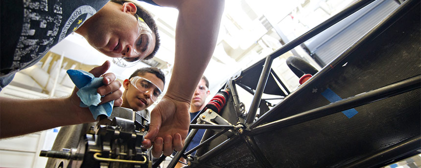 Three young men working on a race car engine